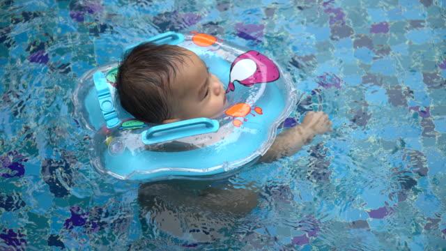 vídeos de stock, filmes e b-roll de bebé aprender a nadar na piscina, vestindo - flutuando na água