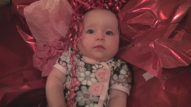 baby lies in christmas wrapping paper - christmas wrapping paper stock videos & royalty-free footage