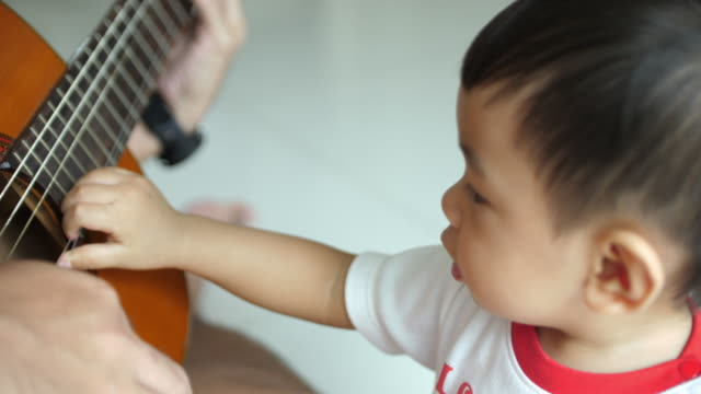 baby listening guitar hero - music therapy stock videos & royalty-free footage