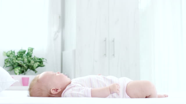 baby lying down at bed - camera dei bambini video stock e b–roll