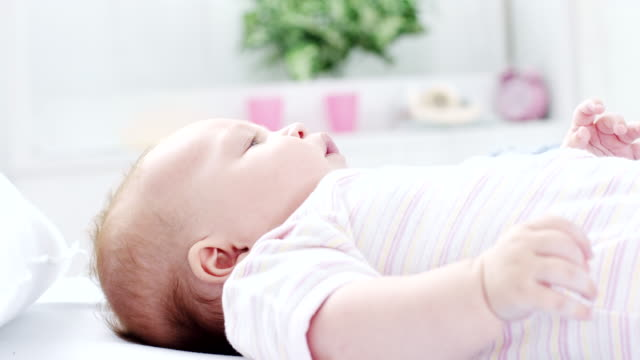 baby lying down in the bed - camera dei bambini video stock e b–roll