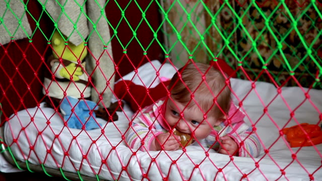 baby lying in the crib and chewing the pacifier - lying on front stock videos & royalty-free footage