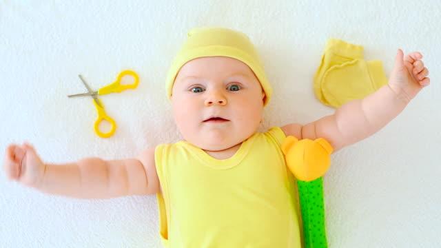 vídeos de stock e filmes b-roll de baby lying next to scissors - só um bebé menino