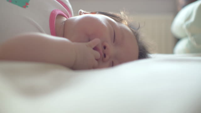 baby lying on bed and playing - cot stock videos & royalty-free footage