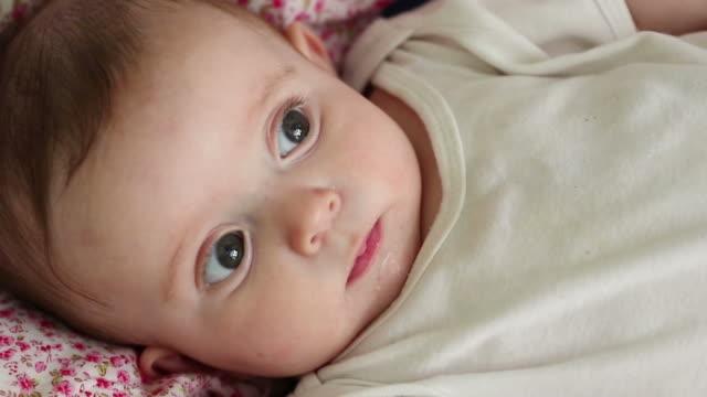 vidéos et rushes de baby lying on bed - vêtement de bébé