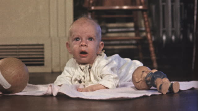1955 ms focus baby lying on front on blanket and looking up/ usa - baby blanket stock videos & royalty-free footage