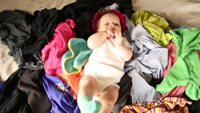 vídeos de stock, filmes e b-roll de a baby lying on her back on top of a pile of clothing. - vida de bebê