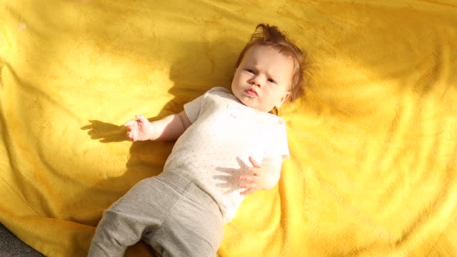 a baby lying on her back with bubbles flying above her. - abbigliamento da neonato video stock e b–roll