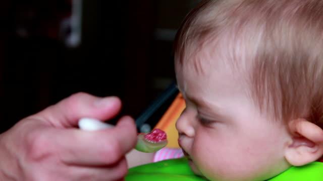 vídeos de stock e filmes b-roll de baby moving away mother hands with food - remover