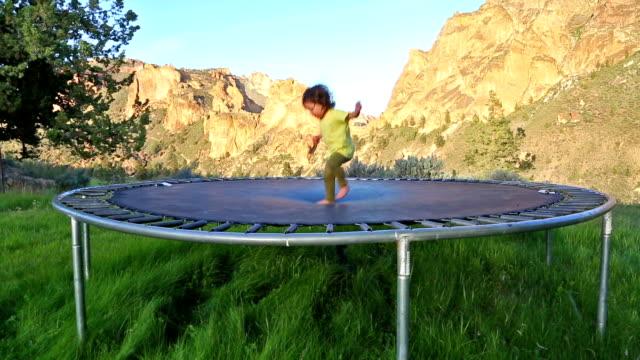 bambino su pedana elastica per saltare - pedana elastica per saltare video stock e b–roll