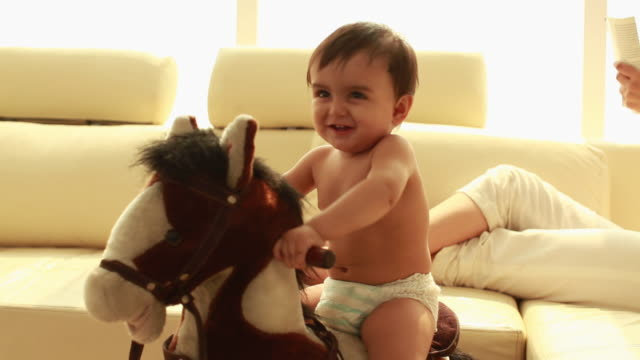 Baby playing on a rocking horse with his mother sitting behind him