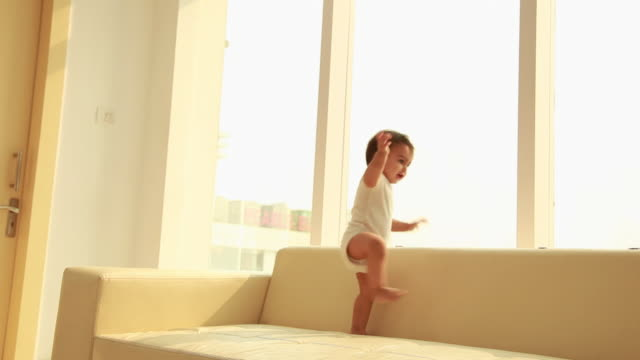 baby playing on a sofa - wide shot stock videos & royalty-free footage