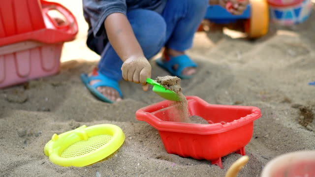 slo mo baby playing sand in sandbox. - 2 kid in a sandbox stock videos and b-roll footage