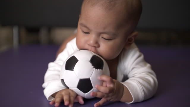 SLO MO Baby playing soccer ball