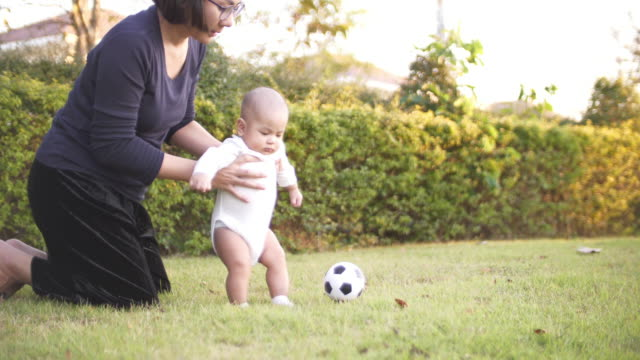 SLO MO Baby playing soccer ball with mother