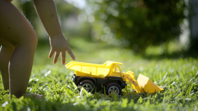 4k baby playing toy truck in front yard under natural sunlight. - babies only stock videos & royalty-free footage
