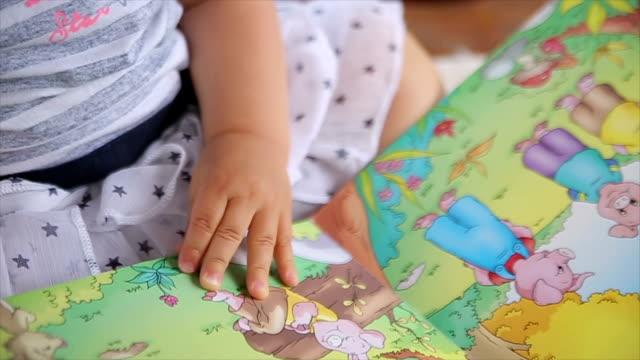 bambino che gioca whit libro illustrato - fiaba video stock e b–roll