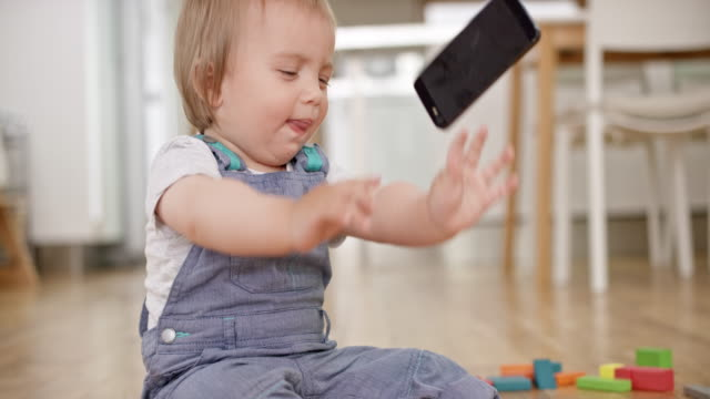 slo mo baby playing with a mobile phone and then throwing it on the floor - lanciare video stock e b–roll