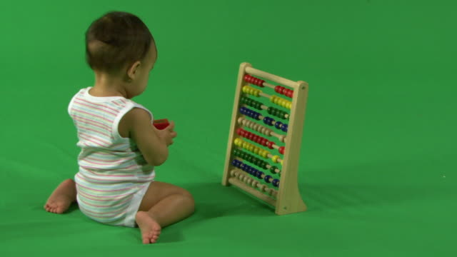 Baby playing with abacus, on green background