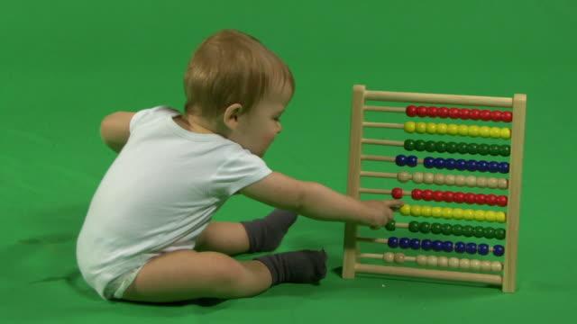 ls baby playing with abacus - ein männliches baby allein stock-videos und b-roll-filmmaterial
