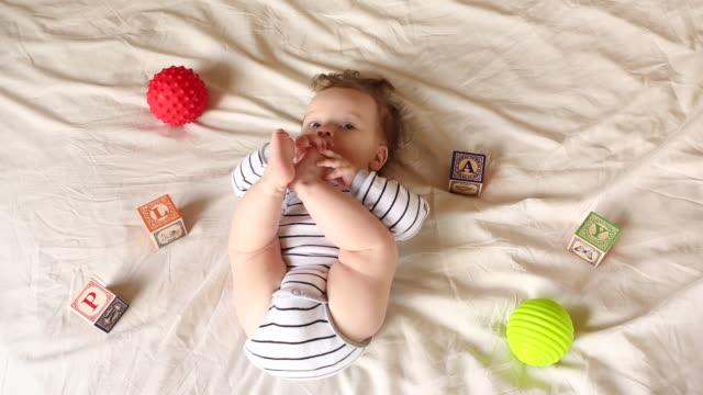 vídeos de stock, filmes e b-roll de a baby playing with balls and toys inside of her home. - vida de bebê