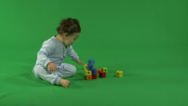 vidéos et rushes de baby playing with building blocks, on green background - jeu de construction
