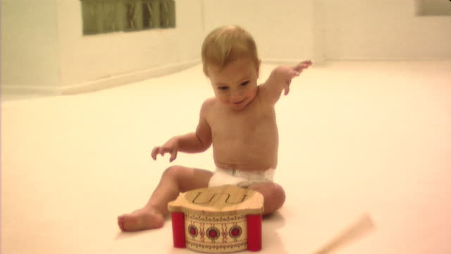 Baby playing with drum