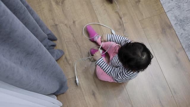 電気延長とワイヤーで遊ぶ赤ちゃん - 引く点の映像素材/bロール