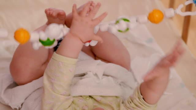 vídeos de stock e filmes b-roll de bebé a brincar com o brinquedo jogo, grande plano - só um bebé menino