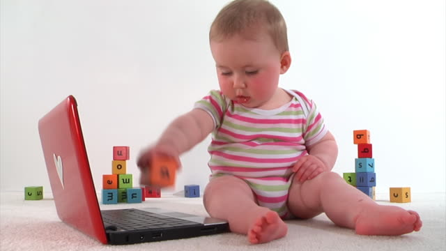 Baby playing with laptop and colour bricks on white background.