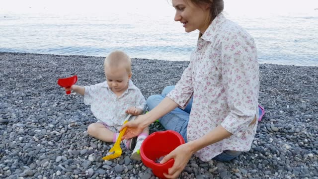 Baby playing with mom on the beach in summer holidays