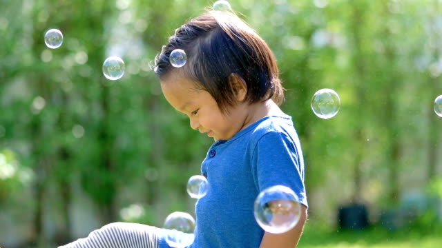 baby playing with soap bubbles outdoors. - lawn stock videos & royalty-free footage