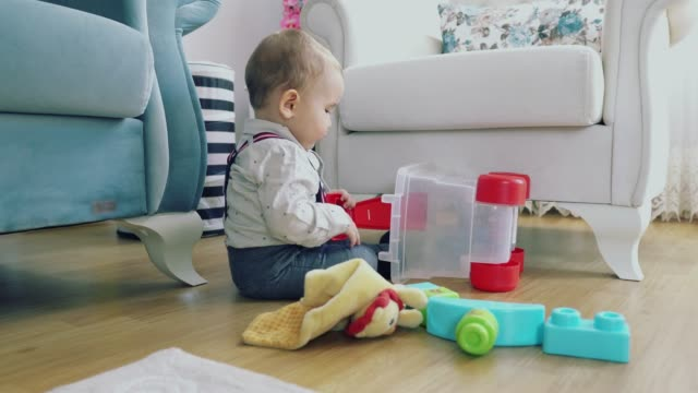 vídeos de stock e filmes b-roll de baby playing with toy - gatinhar