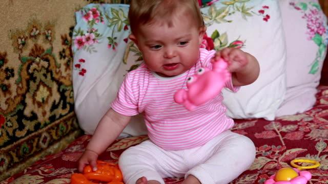 barnet leker med leksaker på sängen - endast en flickbaby bildbanksvideor och videomaterial från bakom kulisserna