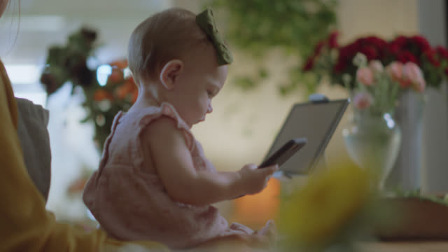 cu. baby plays with florist mom's phone while she tries to get work done - baby girls stock videos & royalty-free footage