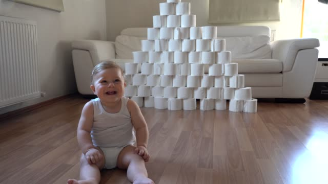 baby plays with toilet papers when she is bored at home during pandemic - tessuto umano video stock e b–roll