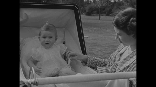 baby prince charles sits in baby carriage while princess elizabeth kneels next to him elizabeth hands him rattle charles holds rattle while looking... - 1949 stock videos and b-roll footage