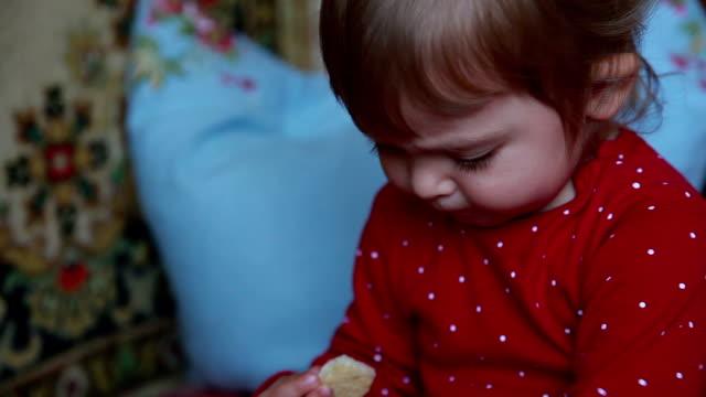 赤ちゃんは、口の中にクッキーの大きい部分を置く