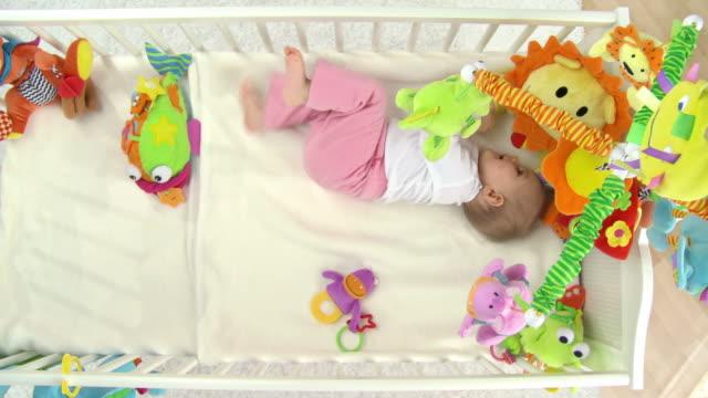 hd crane: baby rolling in crib - crib stock videos & royalty-free footage