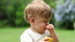 Baby scratching nose with hand. Infant boy touching face