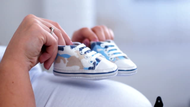 baby shoes on pregnant belly - baby human age stock videos and b-roll footage