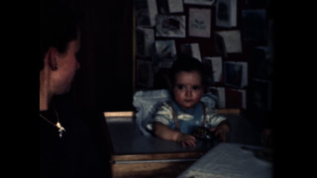 baby sits in highchair and plays with a toy wind-up beetle. - 1940 1949 stock-videos und b-roll-filmmaterial