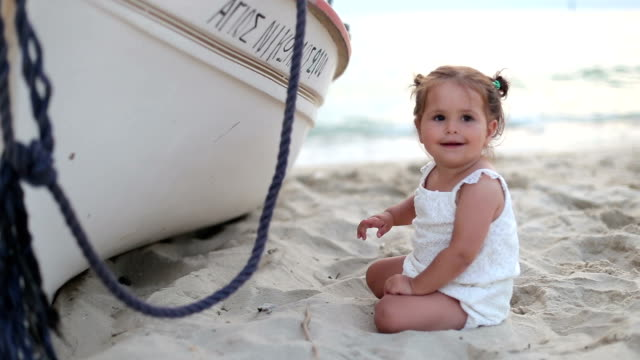 Baby sitting and playing on the beach by the boat - pointing with her hand