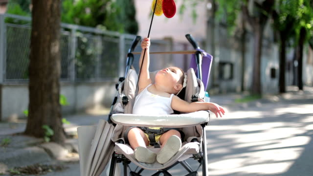 baby sitting in a stroller and playing with rainbow windmill ,pinwheel