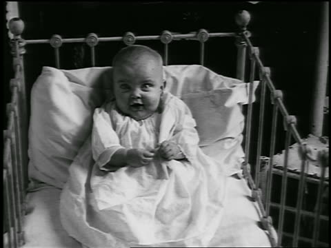 stockvideo's en b-roll-footage met b/w 1920 baby sitting in crib (jump cuts) / detroit, michigan / newsreel - 1920