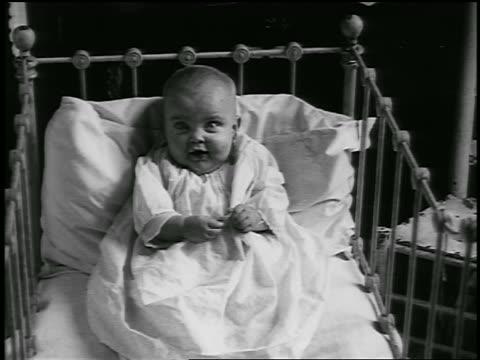 b/w 1920 baby sitting in crib (jump cuts) / detroit, michigan / newsreel - 1920 stock videos & royalty-free footage