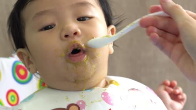 vidéos et rushes de bébé assis dans la chaise haute et manger à la maison - nourrir