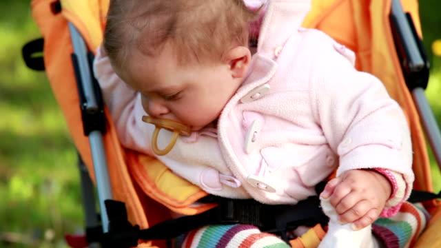 vidéos et rushes de bébé assis dans le landau et regardant avec curiosité - série d'émotions