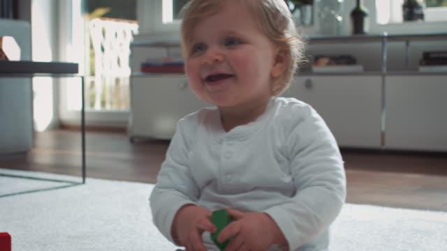 baby sitzt auf teppich - kleinstkind stock-videos und b-roll-filmmaterial