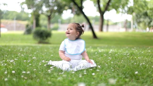 vídeos y material grabado en eventos de stock de bebé sentado sobre hierba para el primer momento de la selección y oler las flores - comida de bebé